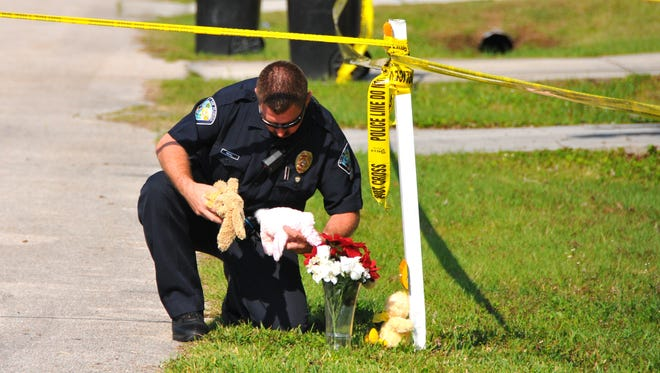 Palm Bay Police Officer John Neal puts stuffed animals at the mailbox in front of a makeshift memorial to the children stabbed at a Palm Bay home.