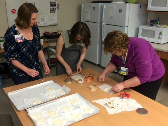 CoxHealth staff members (from left to right) Sarah Bethurem, Lara Ellis and Kathi Long cut out ornaments in various shapes such as circles, stars and Christmas trees.