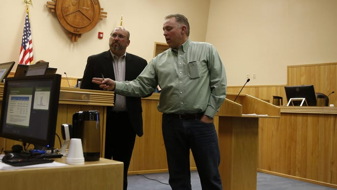 Farmington Electric Utility Director Hank Adair, left, and Farmington resident Brandt Thrower talk to utility consultants through a telephone during Tuesday's City Council meeting in Farmington.