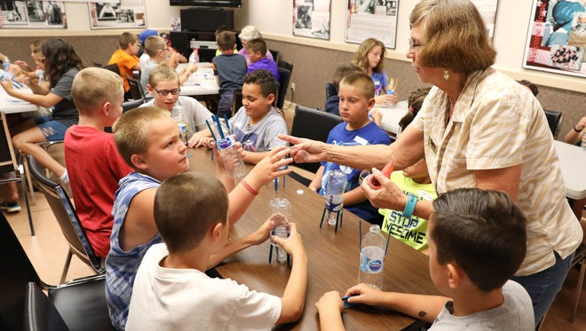 Connie Dingus hands out tape to build rockets during the Reach for the Stars Space Camp at the John and Annie Glenn Historic Site in New Concord.