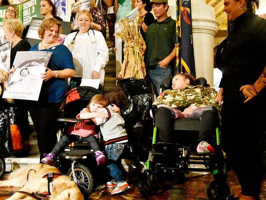 Julie Michaels, front left, of Connellsville, and Jessica Hawkins, right, of Pittsburg, look on as Hawkins' son Lucciano, 2, right center, gives a hug to Michaels' daughter Sydney, 5, left center, as supporters gather at the Pennsylvania State Capitol Building to promote the legalization of medical cannabis in Harrisburg, Pa. on Tuesday, Sept. 22, 2015.   Dawn J. Sagert - dsagert@yorkdispatch.com