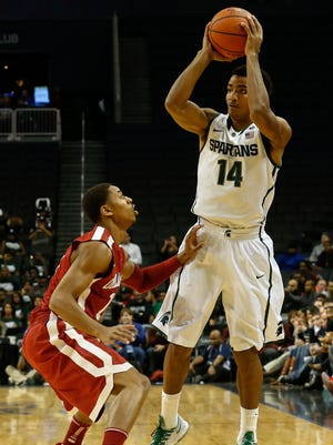 Oklahoma Sooners guard Isaiah Cousins (11) defends Michigan State Spartans guard Gary Harris (14) during the first half at Barclays Center.