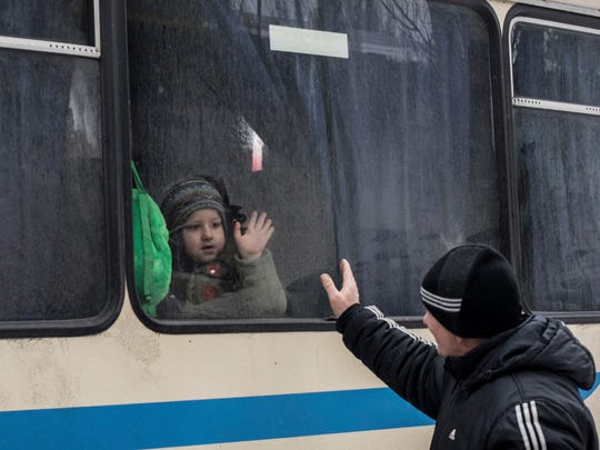 Children wave through a bus window to their relatives in Avdiivka, Ukraine, as they wait to be evacuated to Sviatohirsk, a town 88 miles away and far from the conflict front line in eastern Ukraine, on Feb. 5, 2017.