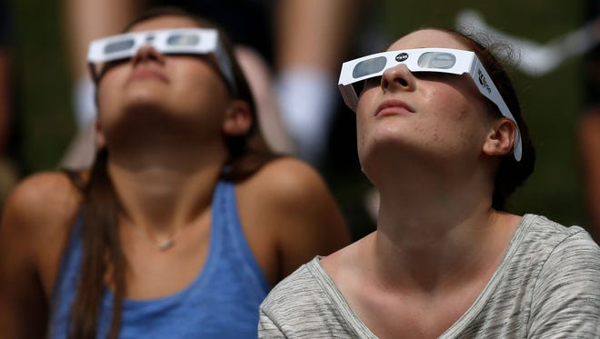 Alex Idalski, left, and Madison Colbrook join others Aug. 21, 2017, to watch the partial solar eclipse from Butler University in Indianapolis.