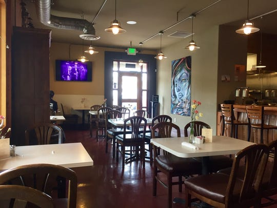 The dining room at Oxbow Café & Bistro features local art and fresh flowers on tables.