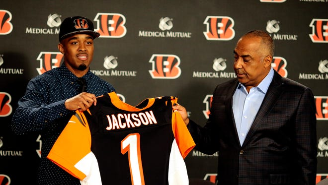 Cincinnati Bengals head coach Marvin Lewis hands off a No. 1 jersey to first round draft pick William Jackson during a press conference at Paul Brown Stadium in downtown Cincinnati on Friday, April 29, 2016. The Houston cornerback was chosen 24th overall.
