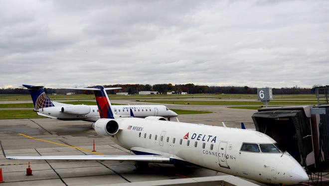 A United Airlines jet taxis behind a Delta plane at the terminal as it makes its way to the runway at the the Capital Region International Airport October 30, 2015.