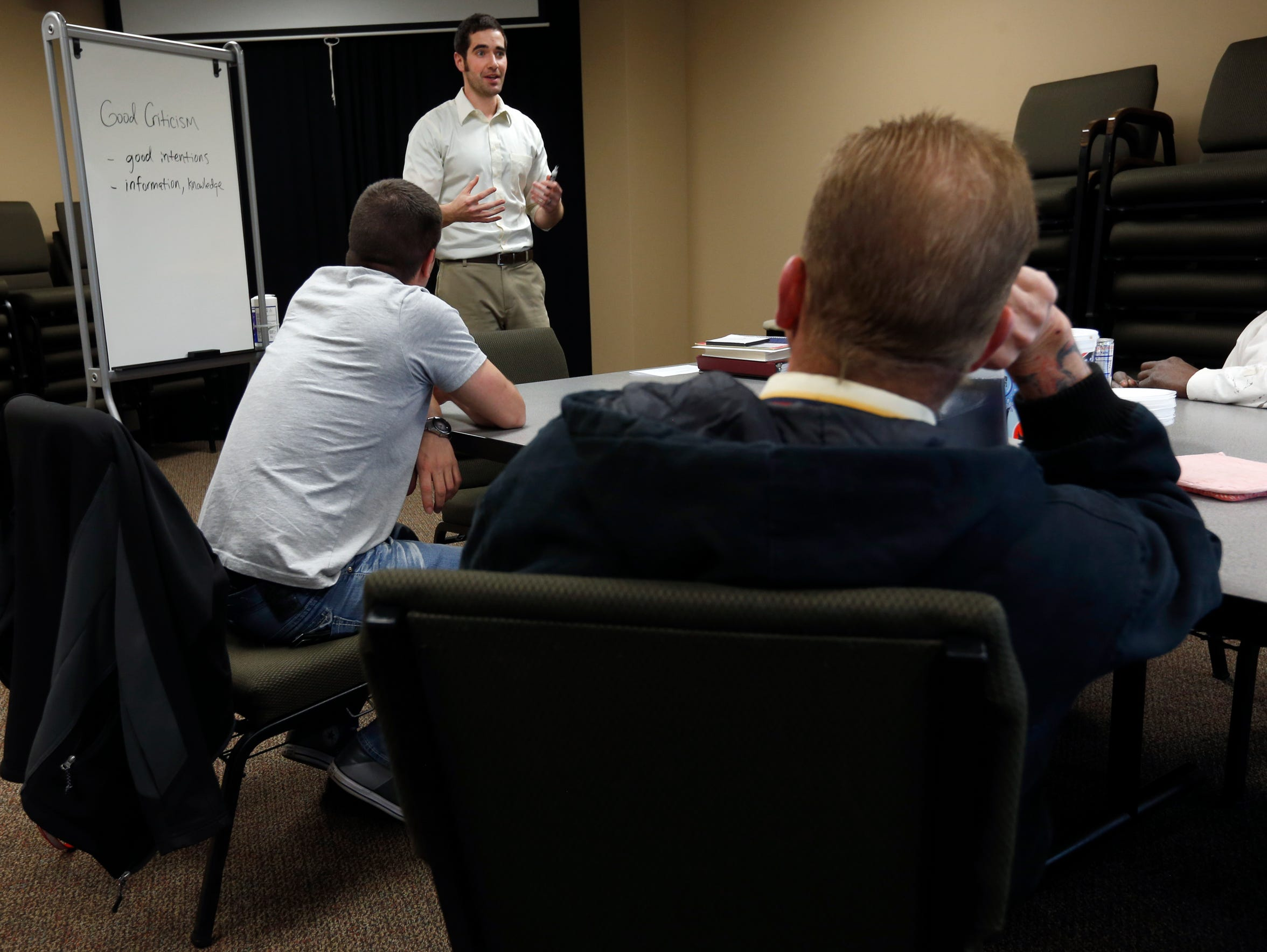 Counselor Austin Boon talks with a group of men about
