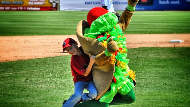 """A fan in a St. Louis Cardinals cap tackles Henry the Puffy Taco during a San Antonio Missions tradition known as """"the Taco Chase."""""""