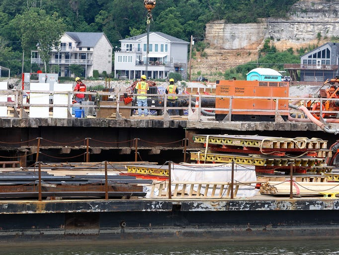 Crews on the Kentucky side of the Ohio River work on barges and temporary structures as they build the east end bridge. June 20, 2014