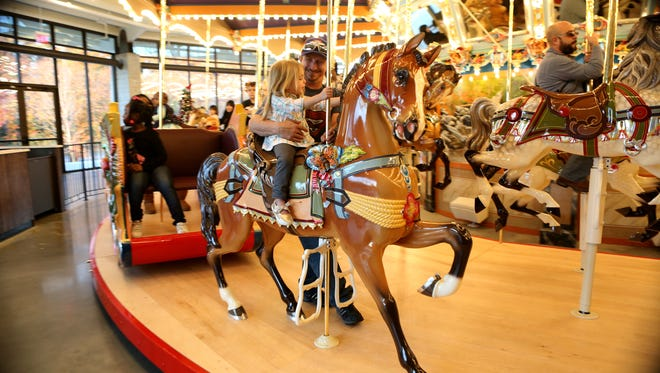 December 2, 2017 - Rodney Worley holds his girlfriend's granddaughter, Kennedi Carson, 2, as she rides on a horse during the grand re-opening of the newly restored carousel at the Children's Museum of Memphis on Saturday.