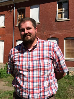 Justin Doyle of Blackbird Investments stands in front of the barracks his company hopes to turn into apartments at Fort Des Moines.