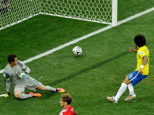 Brazil's Marcelo, right, scores an own goal past Brazil's goalkeeper Julio Cesar during the group A World Cup soccer match between Brazil and Croatia, the opening game of the tournament, in the Itaquerao Stadium in Sao Paulo, Brazil, Thursday, June 12, 2014. (AP Photo/Thanassis Stavrakis)