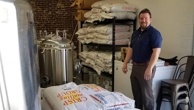 Henderson Brewing Company's Doug Laramie is surrounded by the microbrewery's first shipment of grain Friday.