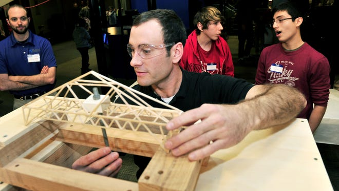 Ross Muirhead, a volunteer with the American Society of Civil Engineers, sets up a bridge on the scales during the sixth annual Nashville Bridge Building Competition, which is part of Adventure Science Center's annual Engineering Day in 2013.