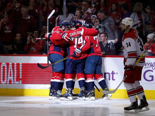Washington Capitals teammates left wing Andre Burakovsky (65), defenseman John Carlson (74) and right wing T.J. Oshie (77) celebrate defenseman Michal Kempny (6) after Kempny scored a goal as Carolina Hurricanes left wing Phillip Di Giuseppe (34) skates by during the second period of an NHL hockey game in Washington, Friday, March 30, 2018. (AP Photo/Carolyn Kaster)