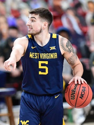 West Virginia's Jordan McCabe (5) controls the ball during the first half of an NCAA college basketball game against Texas Tech in Lubbock, Texas, Tuesday, Feb. 9, 2021. (AP Photo/Justin Rex)