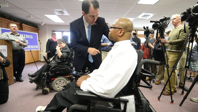 Wisconsin Gov. Scott Walker speaks with Byia Martin, a coordinator for Options for Independent Living, at a 2014 event announcing the expansion of Family Care under Medicaid.