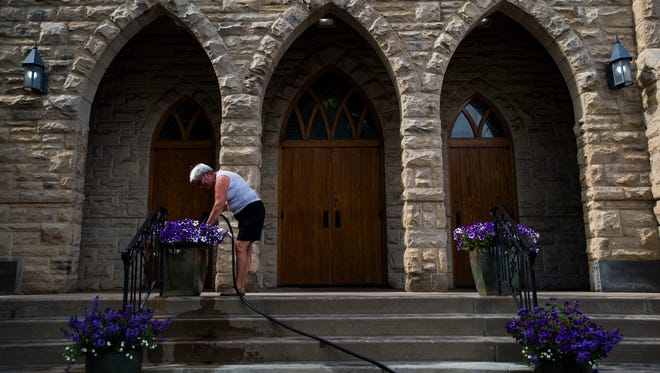 St Joseph's Catholic Church's gardener Ellie Dvorak waters the petunia's planted outside the main entrance on Friday, June 15, 2018, in Fort Collins, Colo.