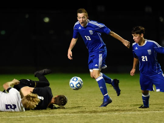 Andrew Cross (13) and Zach Rohrscheib of Memorial rush for the ball after Bloomington South goal keeper Nathan Pliske and his teammate John Bannes land on the ground during the second half of the Boys 2A regional at Jasper High School Thursday.  Memorial won on penalty kicks to advance.