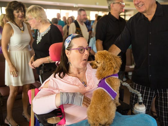Renee Whisner's dog, Peyton, sits politely with her throughout service at the Unity of Naples church on Sunday, Oct. 1, 2017.