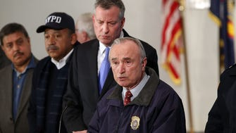 New York City Police Commissioner William Bratton is joined by Mayor Bill de Blasio at a news conference at Woodhull Hospital following the killing of two New York City police officers  on Saturday.