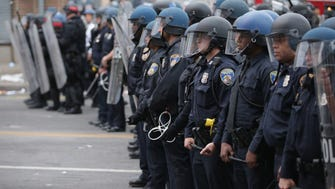 A line of Baltimore police officers hold their ground at the corner of Pennsylvania and North avenues during violent protests following the funeral of Freddie Gray April 27, 2015 in Baltimore.
