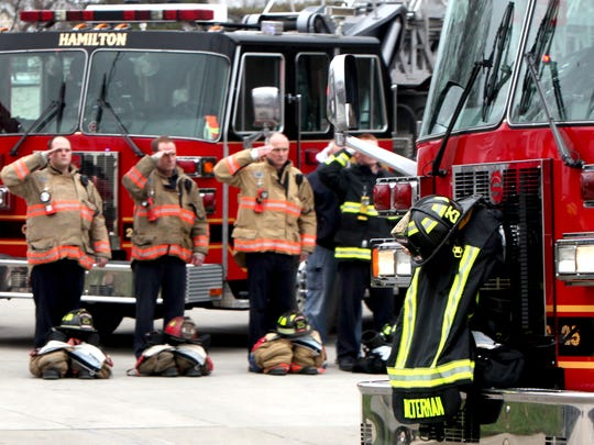 Firefighters salute as Patrick Wolterman's casket passes by the Company 25 fire station in Hamilton Thursday. The procession from Princeton Pike Church of God to Spring Grove Cemetery included representatives from dozens of area fire departments.