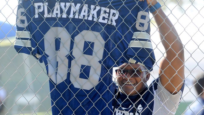 A Cowboys fan holds up a jersey during the 2016 training camp in Oxnard.