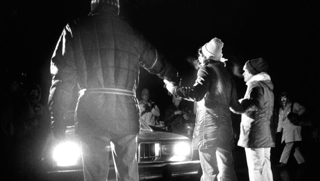 Three of the four protesters arrested Dec. 1, 1983, block the entranced to Williams International Corp.