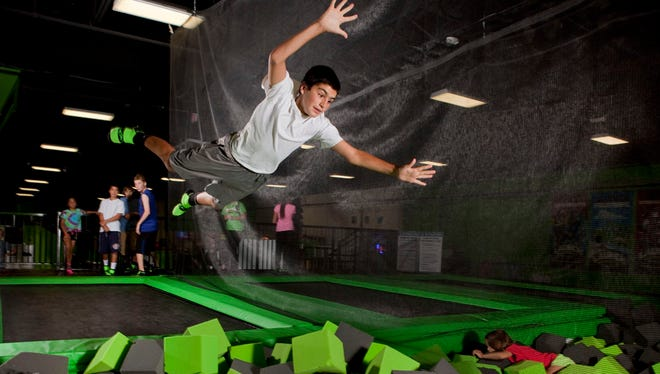 A young man jumps into a foam pit at a Launch Trampoline Park.