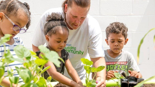 Aramark volunteer Karen Sachs, center, with preschoolers Desiree Vaughn, left, Ayanna Mills and Christian Perez, work together on an urban garden at Morristown Neighborhood House, in collaboration with Cornerstone Family Programs.