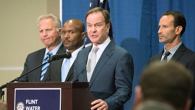 Genesee County Prosecutor David Leyton, Deputy Chief Investigator Ellis Stafford, and Special Assistant Attorney General Noah Hall behind the podium during Michigan Attorney General Bill Schuette's announcement of a civil suit against Veolia, engineering services corporation, for negligence in the Flint water crisis at a press conference at University of Michigan Flint in Flint, Michigan on June 22, 2016.
