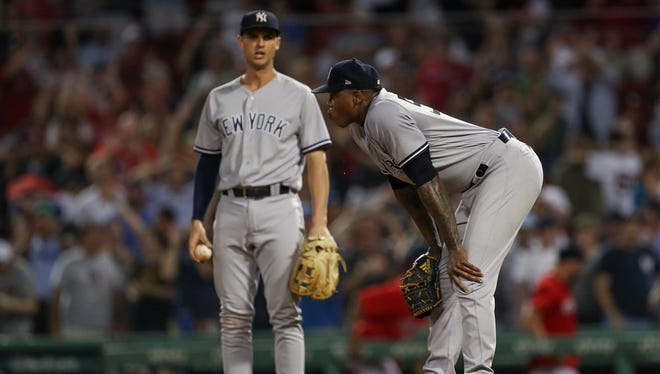 New York Yankees relief pitcher Aroldis Chapman (54) reacts after giving up the tying run as first baseman Greg Bird (33) looks on during the ninth inning against the Boston Red Sox at Fenway Park.