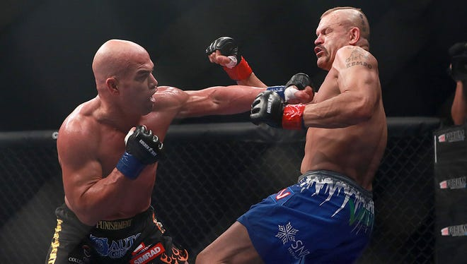 Tito Ortiz (left) punches Chuck Liddell during the third fight of their trilogy in the headliner of Golden Boy's first MMA event.
