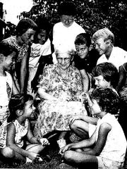 Mabel Wolcott is seen with children who helped raised
