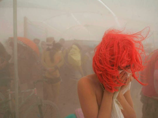 A woman tries to shelter herself during a dust storm on the playa of the Black Rock Desert in Gerlach, Nev., during the 2007 Burning Man festival.