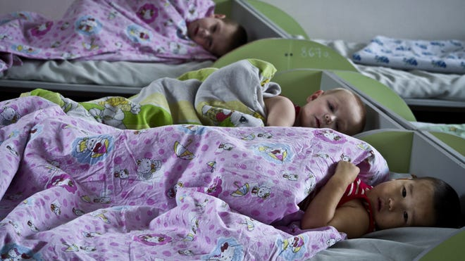 Orphans are in bed in an orphanage in Bishkek, Kyrgyzstan, earlier this year.  Americans were in the process of adopting 65 orphans from Kyrgyzstan when it suspended international adoptions.