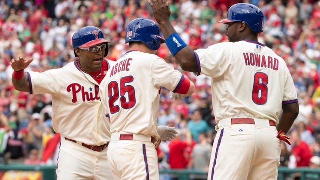 Philadelphia Phillies' Cody Asche, center, gets congratulations from Marlon Byrd, left, and Ryan Howard, right, after hitting a three run home run during the seventh inning of a baseball game against the Cincinnati Reds, Sunday, May 18, 2014, in Philadelphia. The Phillies won 8-3. (AP Photo/Chris Szagola)