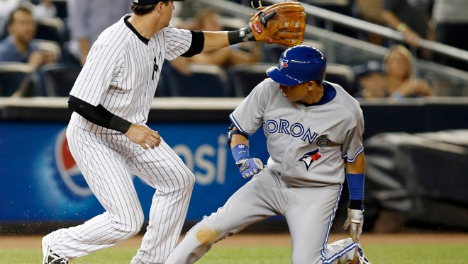 Yankees third baseman Kelly Johnson waits for the throw from left field as the Blue Jays' Munenori Kawasaki slides into third with a ninth-inning triple off closer David Robertson in the Blue Jays' 3-1 loss Tuesday night.