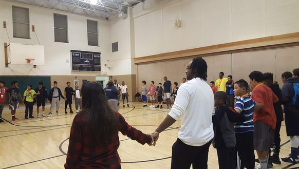 Students hold hand in a prayer circle before leaving
