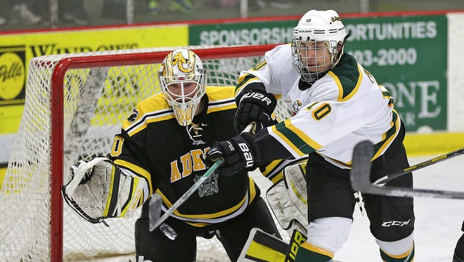 St. Norbert College forward Ross Pavek (10) tries to deflect a shot past Adrian College goalie Tyler Parks during a Jan. 22 game at Cornerstone Community Center in Ashwaubenon. Pavek is one of nine players with at least 20 penalty minutes this season.