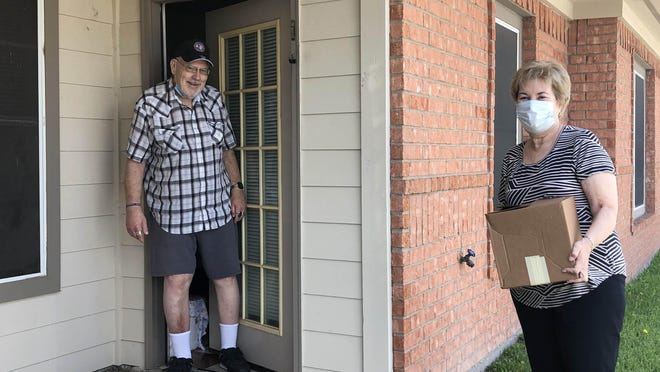 Volunteer for Meals on Wheels of Erath County Chris Martin delivers a meal to senior citizen Bob Ables.