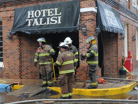 Firefighters stand outside the Hotel Talisi after extinguishing