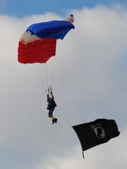 StateSkydiver carrying a POW flag.