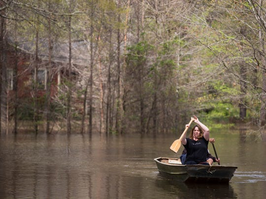 Melissa Anderson paddles a boat as water from Caddo