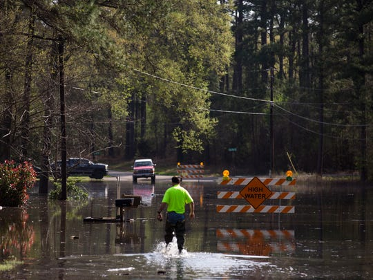 A man walks through floodwaters from Caddo Lake on