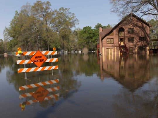 Water from Caddo Lake floods a road and homes in a