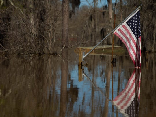 An American flag flies above floodwater on Butler Camp