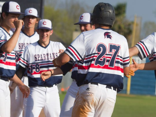 Comeaux players congratulate Colin Thibodeaux, #27, after he scored a run against North Vermilion's in the fifth inning March 15, 2016, 2016.